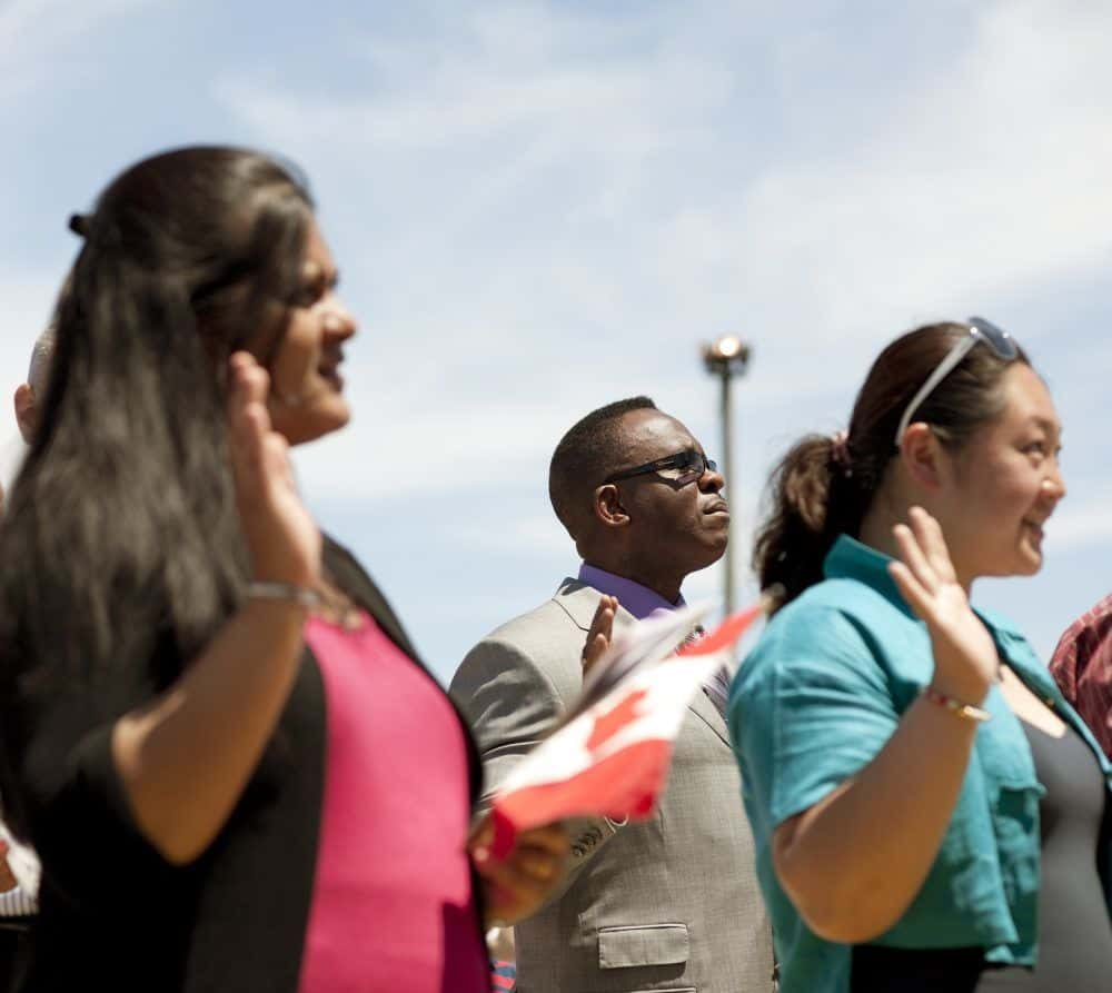 "Milton, Canada - July 1, 2011: New Canadian Citizens are sworn in during a Canada Day new citizenship ceremony at Milton, Ontario fairgrounds the morning of July 1st, 2011. July 1st--or ""Canada Day""--is the national day of Canada. The ceremony included new citizens who had immigrated from a variety of regions and countries including; Afghanistan, Pakistan, India, Nigeria, Australia, Great Britain, South Africa, Iraq, and China."
