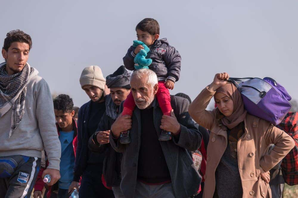 Rigonce, Slovenia - October 26, 2015: Refugee group arrived from Croatia near Rigonce is transferred through the fields to the nearby refugee camp. The group of about 4.000 persons is composed mainly of syrian and iraqi families and afghan and iranian young adults.