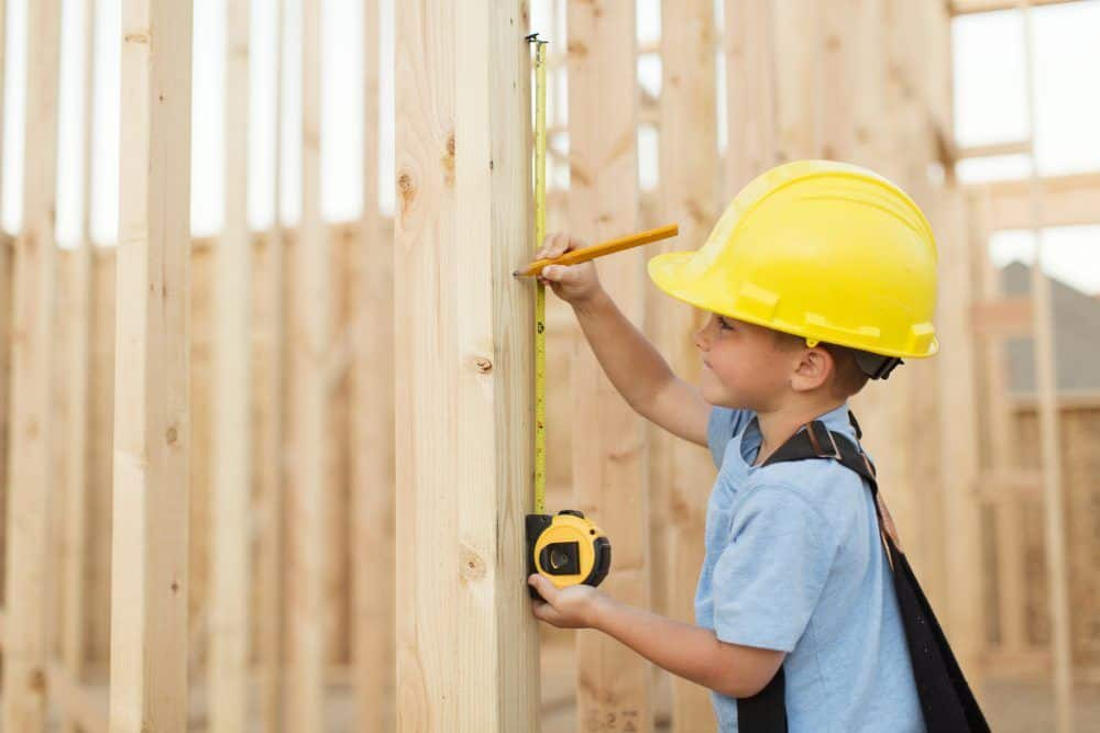 A young boy uses a measuring tape and dreams of being a construction worker. He is wearing a hard hat, suspenders and a tool belt while measuring on a stud of a house being built in Utah, USA.