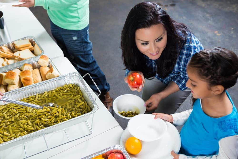 Hispanic mother helps daughter fill her plate at community soup kitchen. The mother is offering her daughter an apple. Trays of food are in front of them. Photo shot from high angle view.