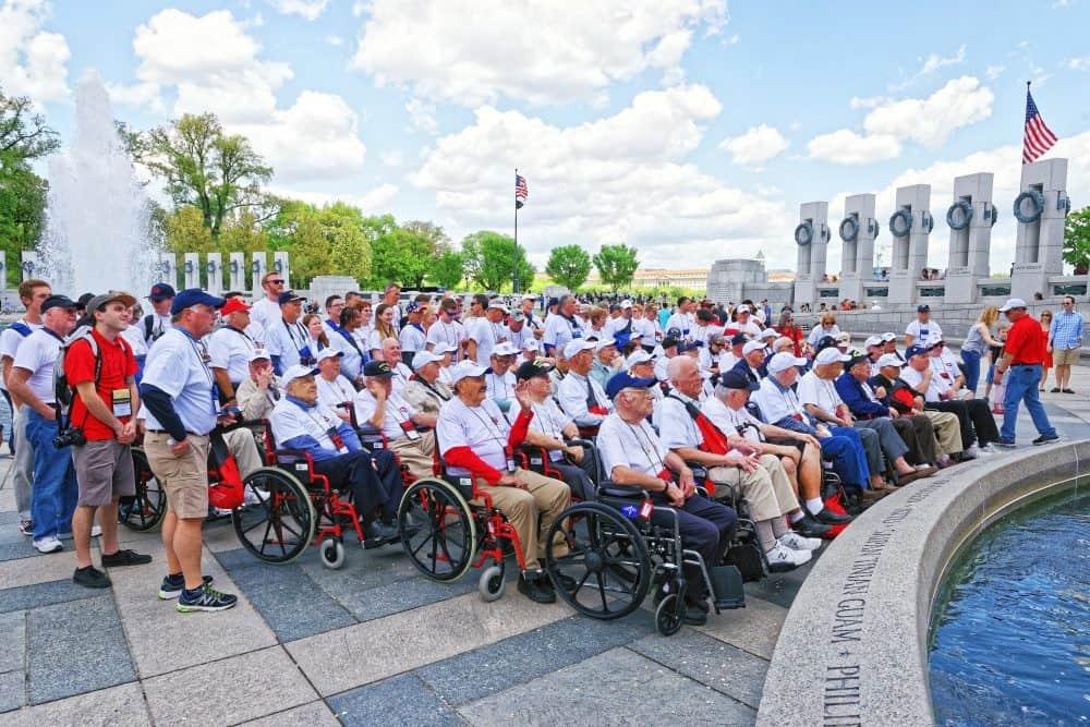Washington DC, USA - May 2, 2015: Tourists and group photo of War Veterans, members of Honor Flight Central Florida nonprofit organization, at Pillars on National World War 2 Memorial, National Mall.