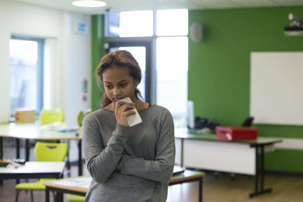 Teenage girl standing in an empty classroom with a mobile phone in her hand. She is looking sad with her arms folded.